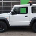 weißer SUZUKI Jimny Automatik mit THE BOSS 200cm V-Pflug und HILLTIP IceStriker 200 als Winterdienstfahrzeug